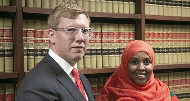 Attorney Andrew Irlbeck, left, stands with client Hamdi Osman in his St. Paul law office. Osman spent five years in federal detention on sex trafficking charges before she was acquitted. Now she is one of six plaintiffs pursuing federal civil suits against a St. Paul police officer, who they say embroiled them in a faked sex-trafficking conspiracy. (Staff photo: Kevin Featherly)