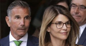 """One example of potentially disqualifying conflicts cited in the Varsity Blues scandal was the fact that Latham & Watkins represents """"Full House"""" actress Lori Loughlin, her husband, fashion designer Mossimo Giannulli, and the University of Southern California — the school they are charged with defrauding. In this photo, Loughlin, front, and Giannulli, left, depart federal court in Boston on April 3 after facing charges in the college admissions bribery scandal. (AP file photo)"""