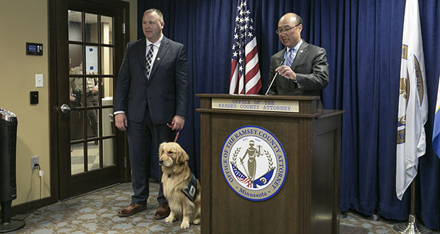 "Ramsey County Attorney John Choi introduces Norie, a laid back but highly trained golden retriever, as his office's new ""facility animal."" The dog will help victims and witnesses stay at ease through the difficult prosecution process. The animal's handler, victim/witness advocate Bill Kubes, is pictured at left. (Staff photo: Kevin Featherly)"