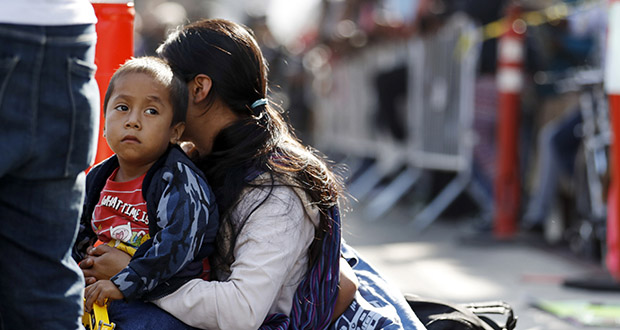 In this July 16, 2019 file photo, a woman sits with her sons as they wait to apply for asylum in the United States along the border in Tijuana, Mexico. The American Civil Liberties Union said Tuesday, July 30, 2019 that more than 900 children have been separated from their families at the border since a judge ordered last year that the practice be sharply curtailed. The ACLU says about one of every five children separated is under 5 years old. (AP Photo/Gregory Bull, File)
