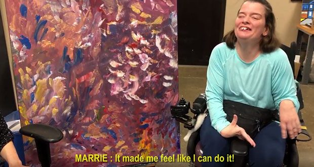 """Plaintiff Marrie Bottelson, an artist who lives with cerebral palsy, wanted in 2013 to integrate deeper into the community. In September 2018 — after the court certified the case as a class action — Bottelson's request was finally granted. In this screen grab from a YouTube video, Bottelson displays her painting, """"Feathers,"""" which she says resulted from an artistic exploration of the way her cerebral palsy naturally causes her brush to move across the canvas. (Parternship Resources Inc. via YouTube)"""