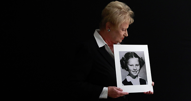 Nancy Holling-Lonnecker, 71, poses with a picture taken of her as a young girl, at her home in San Diego. Holling-Lonnecker plans to take advantage of a three-year window in California that allows people to make claims of sexual abuse no matter how old. (AP photo: Gregory Bull)