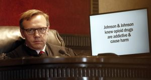 In this May 28 photo, Judge Thad Balkman listens during opening arguments in Norman, Oklahoma, as a slide from the state's presentation is displayed on a monitor in the trial against drugmakers blamed for contributing to the opioid crisis. (AP file photo)