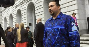 In this March 13, 2019, file photo, Tehassi Hill, tribal chairman of the Oneida Nation, stands outside a federal appeals court in New Orleans, following arguments on the constitutionality of a 1978 law giving Native American families preference in adoption of Native American children. (AP Photo/Kevin McGill, File)