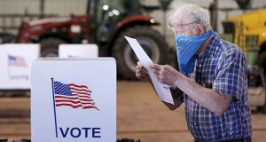 Robert Wilson reviews his selections on his ballot while voting at the highway garage building Tuesday, April 7, in Dunn, Wisconsin. A partisan fight over voting in Wisconsin was the first issue linked to the coronavirus to make it to the Supreme Court. (John Hart/Wisconsin State Journal via AP)