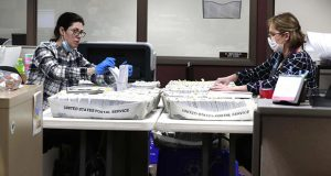 From left Katherine Katsekes, and Diane Scott, both paid volunteers, help sort absentee ballots by ward March 31 at Brookfield City Hall. The ballots will be opened on election day, April 7. (Milwaukee Journal-Sentinel via AP)