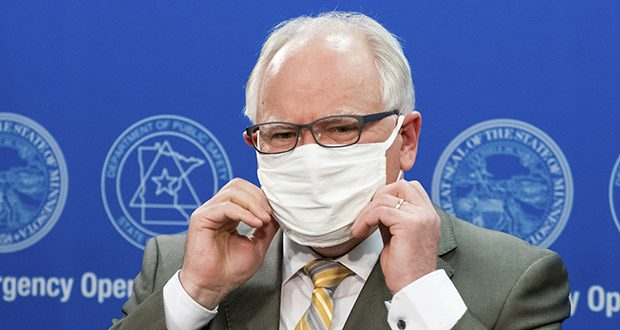 Gov. Tim Walz puts his mask back on at the conclusion of a press conference Tuesday. GOP House Minority Leader Kurt Daudt has threatened to block the bonding bill unless Walz ends the peacetime emergency over the COVID-19 pandemic. (Star Tribune via AP, pool)