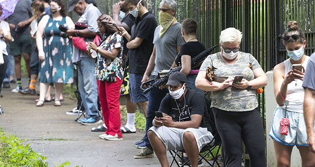 Voters check their phones June 9 as they wait in line to cast ballots at Central Park in Atlanta. Voters reported wait times of three hours. (AP photo: John Bazemore)