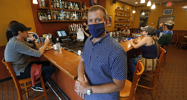 Nick Gavrilides, the owner of the Soup Spoon, poses July 16 at one of his two restaurants in Lansing, Michigan. A Michigan state judge sided with an insurer's rejection of a claim for $650,000 for two months of losses that Gavrilides said he suffered at his restaurants. (AP Photo: Paul Sancya)