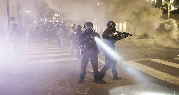 Federal officers deploy tear gas and crowd control munitions at demonstrators during a Black Lives Matter protest at the Mark O. Hatfield United States Courthouse Tuesday, July 28, 2020, in Portland, Oregon. (AP photo: Marcio Jose Sanchez)
