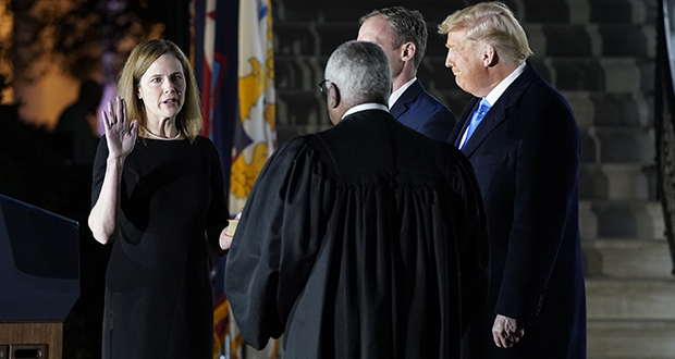 President Donald Trump watches as Supreme Court Justice Clarence Thomas administers the constitutional oath to Amy Coney Barrett on the South Lawn of the White House in Washington on Monday after Barrett was confirmed by the Senate earlier in the evening. (AP photo)