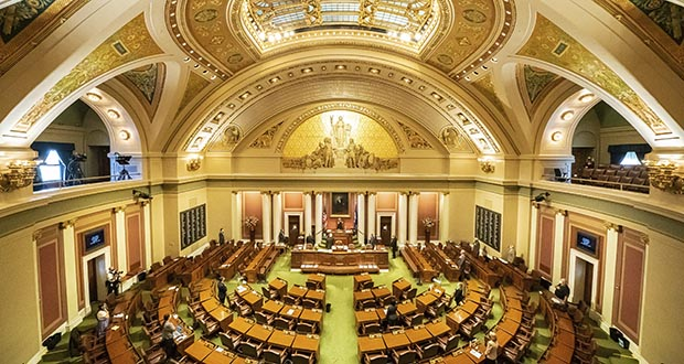 With most legislators working remotely, members present on the House floor stand for the Pledge of Allegiance on Monday for the start of the fifth special session of the year at the Capitol in St. Paul. (Star Tribune via AP)
