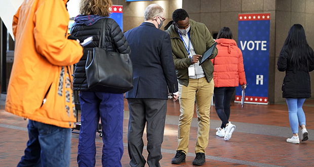Secretary of State Steve Simon has urged voters not to put any more absentee ballots in the mail and instead deliver them in person. In this photo, voters check in to vote at the Hennepin County Government Center on Tuesday, Oct. 27, in Minneapolis as early voting began for county residents. (AP photo: Jim Mone)