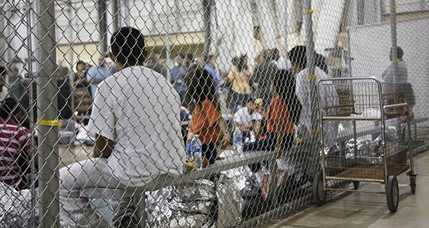 In this June 2018 file photo provided by U.S. Customs and Border Protection, people who have been taken into custody by immigration authorities sit in one of the cages at a facility in McAllen, Texas. (U.S. Customs and Border Protection via AP)