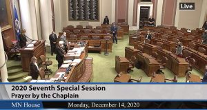 The few members of the Minnesota House in attendance at the Capitol during Special Session VII listen to the chaplain's prayer at the session's opening on Monday. (Photo courtesy of House Public Information Services)