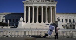 A person walks by newly placed barricades around the Supreme Court Building on Thursday, the day after violent protesters loyal to President Donald Trump stormed the U.S. Capitol in Washington. (AP photo: Evan Vucci)
