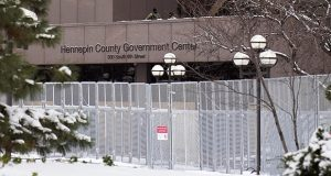 Two National guard soldiers, top, stand watch Tuesday inside the fenced-in perimeter of the Hennepin County Government Center in Minneapolis, where jury selection continues in the trial of former Minneapolis police officer Derek Chauvin. (AP photo: Jim Mone)