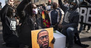 Cortez Rice, left, of Minneapolis, sits with others in the middle of Hennepin Avenue on March 7 in Minneapolis to mourn the death of George Floyd. (Jerry Holt/Star Tribune via AP)