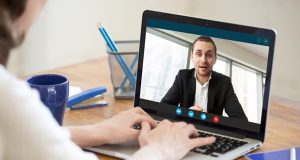 Businesswoman making video call to business partner using laptop