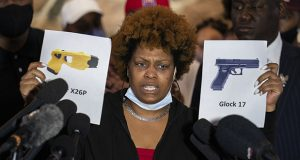 Naisha Wright, aunt of the deceased Daunte Wright, holds up images depicting X26P Taser and a Glock 17 handgun during a news conference at New Salem Missionary Baptist Church on Thursday, April 15, in Minneapolis. (AP photo: John Minchillo)