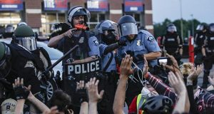 A police officer points a hand cannon at protesters