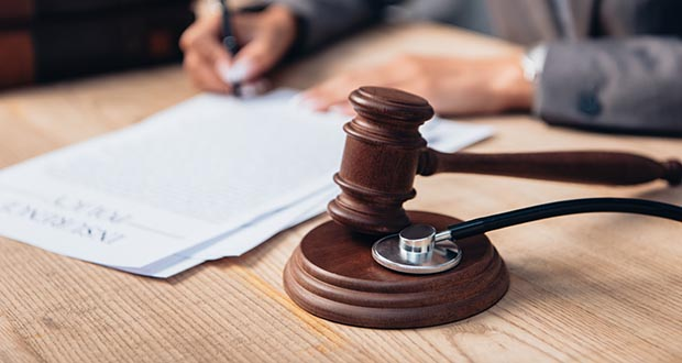 Image of a stethoscope and gavel on a desk with a person writing on a piece of paper in the background