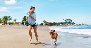 Woman and dog running near the waterline on a beach