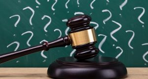 Gavel on a wooden desk in front of a chalkboard full of question marks