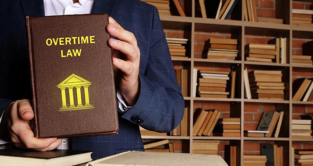 """Attorney holding a book titled """"Overtime Law"""""""