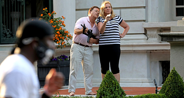 In this June 28, 2020, file photo, armed homeowners Mark and Patricia McCloskey, standing in front their house, confront protesters marching to St. Louis Mayor Lyda Krewson's house. (AP file  photo)