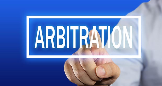Business concept image of a businessman clicking Arbitration button on virtual screen over blue background