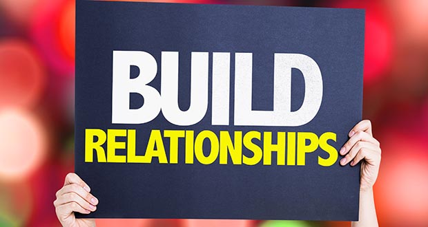 A person holding a sign that says 'Build relationships'