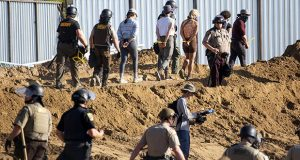 Activists are walked through an Enbridge Line 3 pump station after being arrested